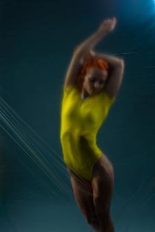 어두운 배경에 노란색 바디수트를 입은 아름다운 소녀 운동선수의 초상화.
