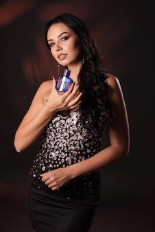 Портрет красивой девушки в платье из черных кристаллов с духами в руках