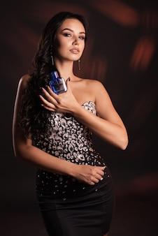Портрет красивой девушки в черном платье с духами в руках