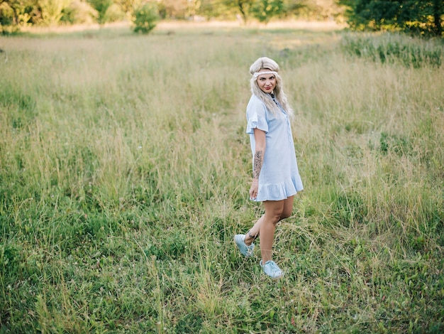 フィールドで青いドレスを着た美しい少女の肖像画