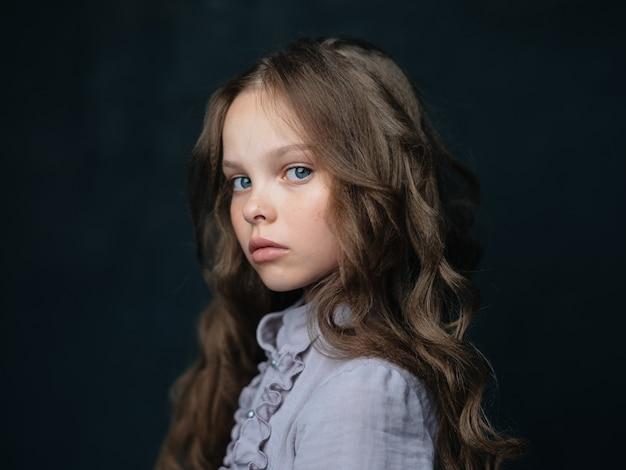 Портрет красивой девушки в сером платье на темном фоне и вьющимися волосами голубыми глазами