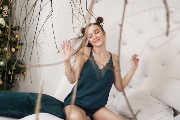 ペニョワールの美しい少女の肖像画。彼女の寝室のベッドの上の美しいセクシーな女性。屋内のファッションモデル。女性の下着。幸せな朝