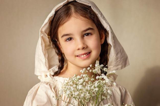 Портрет красивой девушки в белой ретро кепке и букет белых цветов гипсофилы