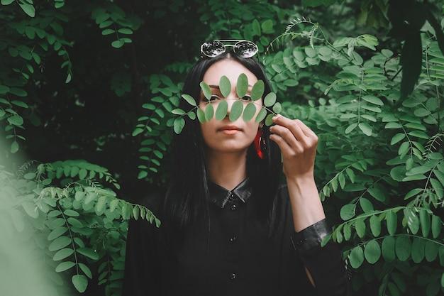 Портрет красивой девушки в черной одежде и очках на фоне зеленых листьев