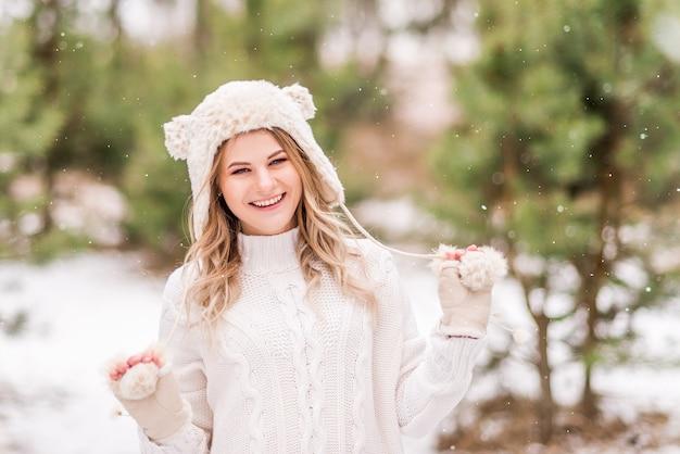 冬の森の薄着の美しい少女の肖像画。女の子は微笑んで雪を楽しんでいます。