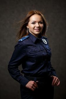 警察の制服を着た美しい少女の肖像画。プロのポーズ