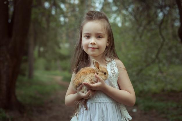 Портрет красивой девушки в лесу. в руках девочка держит кролика.