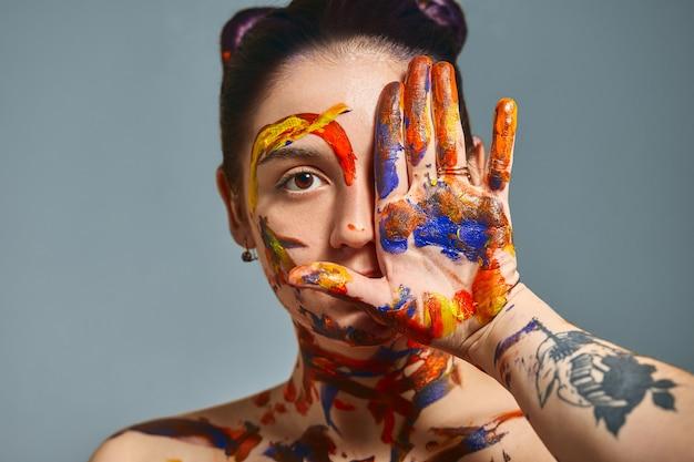 塗料で美しい少女の肖像画。顔を持つ少女と別の塗料で手のクローズアップの肖像画。ファッションアートコンセプト、美容、創造的な人々フリーランスの人々