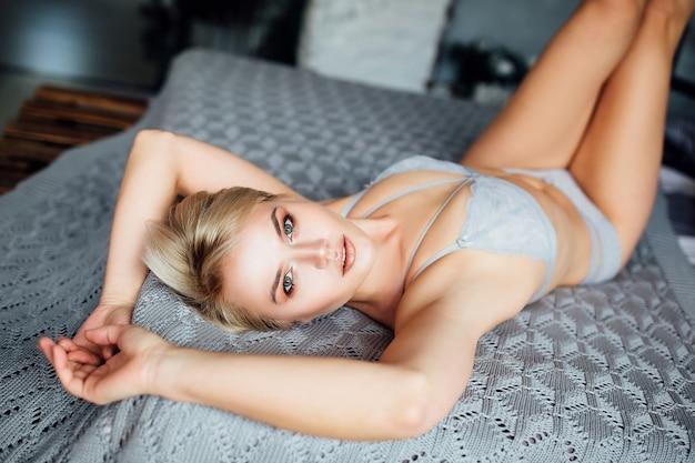 ゲイリーランジェリーを着て、白いベッドに横たわっている美しい少女の肖像画。