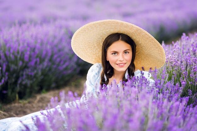 ラベンダーの背景に美しい少女の肖像画。若いモデル。太陽の下での夏の写真