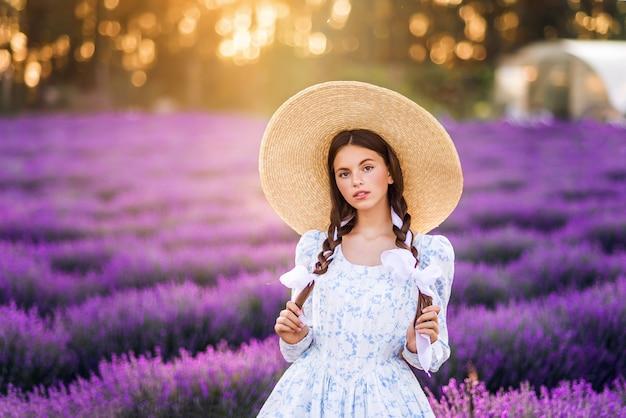 라벤더 배경에서 아름 다운 여자의 초상화. 그녀는 하얀 드레스와 큰 모자를 쓰고 있습니다. 태양의 여름 사진