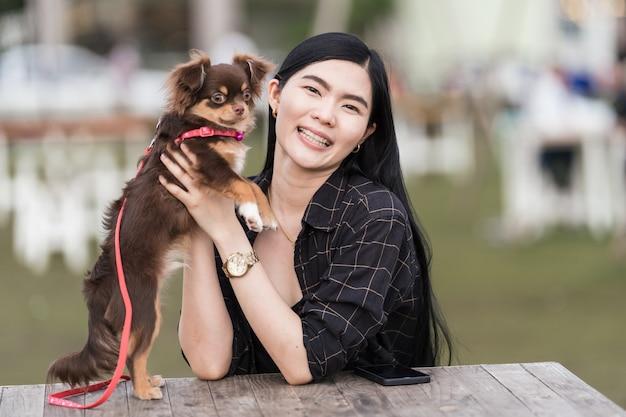 공원에서 야외에서 사랑스러운 강아지와 놀고 있는 아름다운 소녀의 초상화. 주인이 있는 작은 개는 공원에서 놀고 즐겁게 하루를 보냅니다. 애완 동물 사랑 스톡 사진