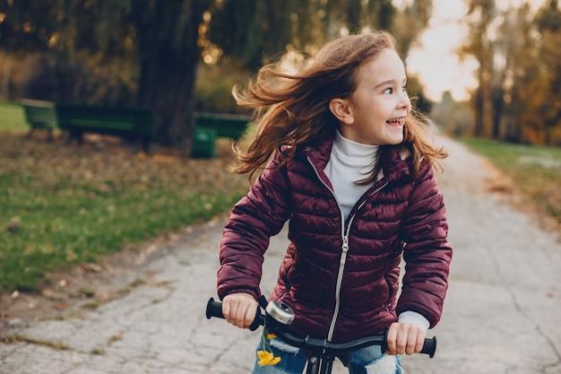 자전거를 타고 공원에서 일몰에 대해 웃고 멀리 보는 아름다운 소녀의 초상화.
