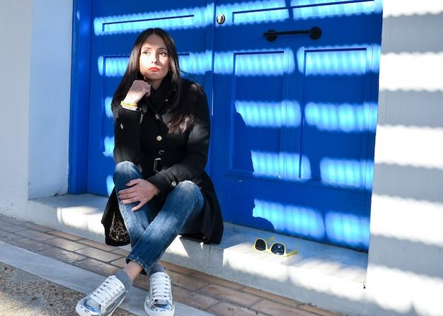 青いドアの近くのコートで床に座っている美しい少女の肖像画
