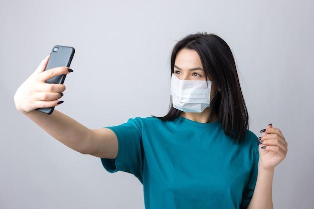 医療マスクを身に着けている灰色の背景に自分撮りをしている美しい少女の肖像画。
