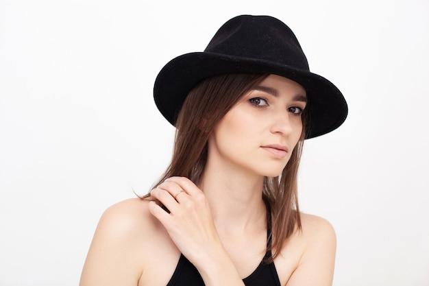 カメラを見ているスタジオで黒い帽子をかぶっている美しい少女の肖像画