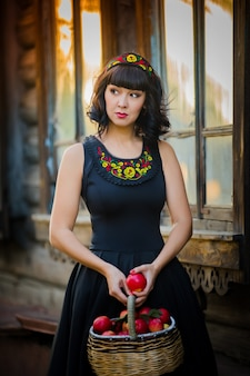 Портрет красивой девушки с корзиной красных яблок в национальном костюме осенью в старом доме