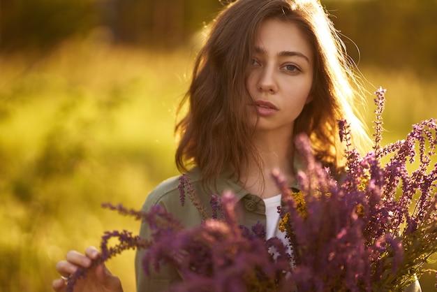 Портрет красивой девушки с букетом лаванды. закатный свет и прекрасная чувственность. девушка наслаждается моментом