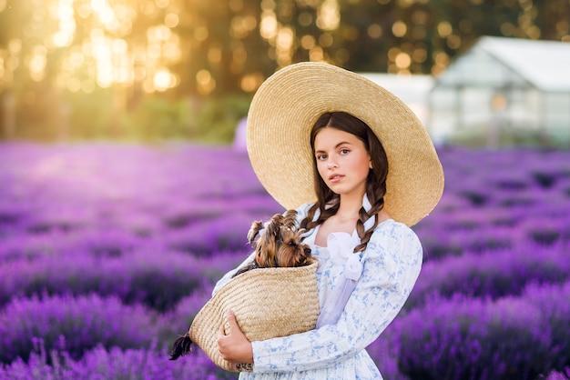 Портрет красивой девушки с собакой в корзине на фоне лаванды. на ней белое платье и большая шляпа.