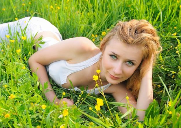 屋外で明るい緑色の目を持つ美しい少女の肖像画。頭を手に草の上に横たわってポーズをとる女性