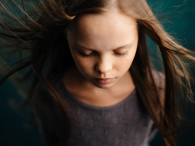 Портрет красивой девушки с закрытыми глазами на бирюзовом фоне и распущенными волосами крупным планом обрезанный вид