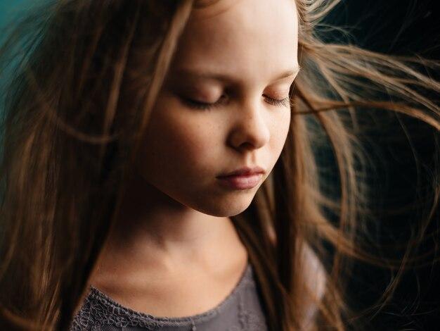 Портрет красивой девушки с закрытыми глазами на бирюзовом фоне и распущенными волосами