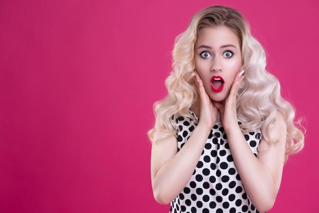 Портрет красивой девушки с вьющимися волосами удивлен и шокирован