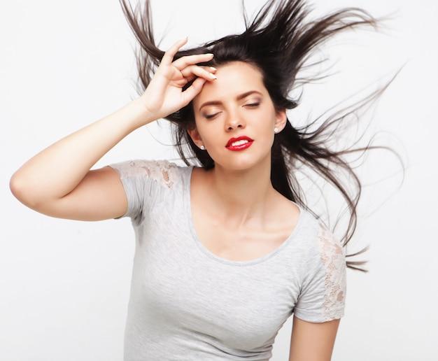 Портрет красивой девушки с развевающимися волосами над белой