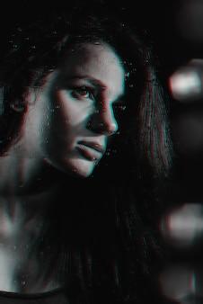 Портрет красивой девушки с эффектом глюка сквозь стекло с каплями дождя