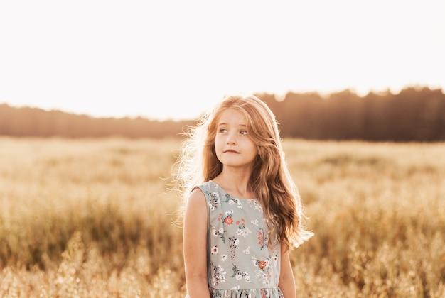해질녘 황금빛 들판에 긴 머리를 한 아름다운 소녀의 초상화