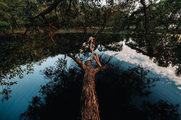 라일락 꽃과 긴 파란색 여름 드레스에 호수에 앉아 긴 머리를 가진 아름 다운 여자의 초상화