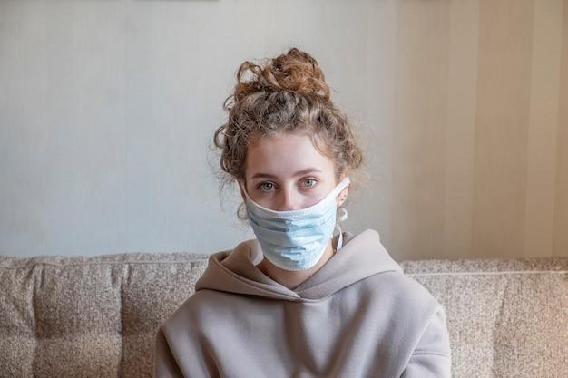 自宅で医療マスクを持つ美しい少女の肖像画。コロナウイルス。