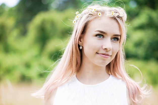들판에 데이지 화환이 있는 분홍색 머리를 한 아름다운 소녀의 초상화