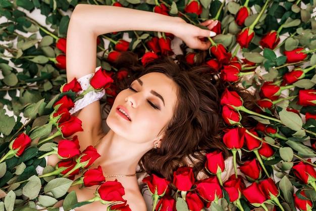 赤い花とバラの美しい少女の肖像画。美容ファッションモデルの女性の顔のクローズアップ。完璧な肌。プロのメイクアップ。形。口紅、ファンデーション、マスカラ広告。