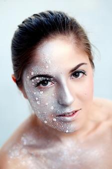 Портрет красивой девушки с серебряным боди-артом на белом фоне