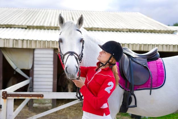 Портрет красивой девушки всадника молодой женщины, стоя возле белой лошади в конюшне в