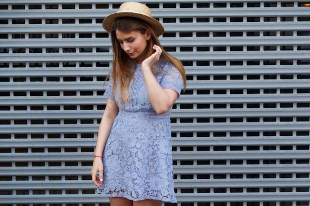 エレガントな帽子と青いレースのドレスで美しい優雅な女性の肖像画。
