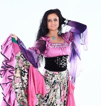 Портрет красивой цыганской танцовщицы исполняет танец на белом фоне