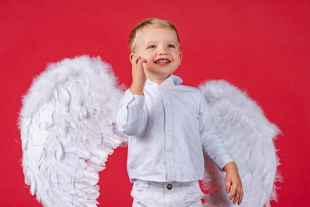 Портрет красивого счастливого мальчика с крыльями ангела.