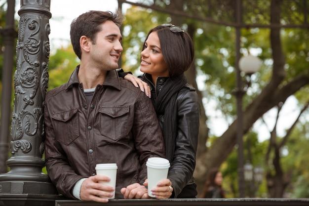 屋外でいちゃつく美しい幸せなカップルの肖像画