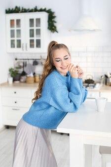 装飾されたキッチンで青いセーターの髪型を持つ美しい幸せなかわいい女の子の肖像画