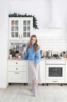 明るいキッチンで青いセーターの髪型を持つ美しい幸せなかわいい女の子の肖像画