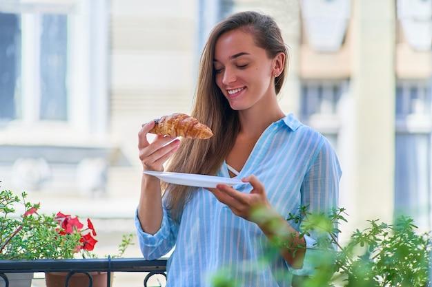 Портрет красивой счастливой милой радостной улыбающейся романтичной женщины со свежеиспеченным круассаном на французский завтрак утром на балконе
