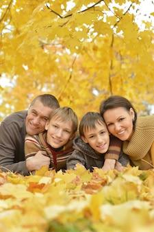 秋の公園に横たわっている美しい幸せな家族の肖像画