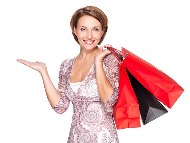Портрет красивой счастливой женщины с жестом презентации и хозяйственными сумками над белым пространством