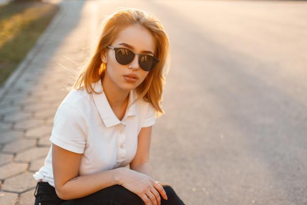 일몰에 검은 청바지에 흰색 폴로 티셔츠에 세련 된 선글라스에 아름 다운 hipster 젊은 여자의 초상화. 미국 여자는 아스팔트 도로에 앉아있다.