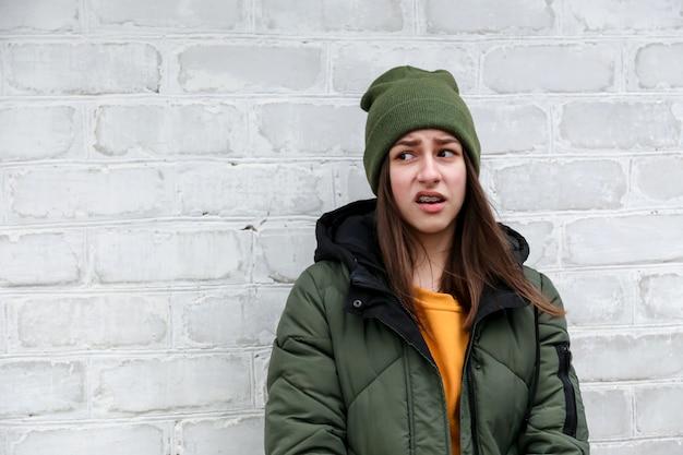 Портрет красивой недоверчивой девушки с расчалками в желтом свитере и хаки шляпе, которая стоит возле белой кирпичной стены. концепция эмоций.