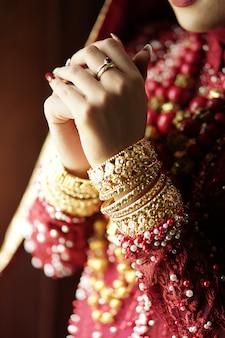금색과 빨간색 드레스기도에 아름다운 인도 신부의 초상화