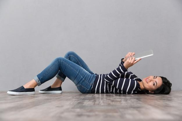 Портрет красивой японской женщины, лежащей на деревянном полу с планшетным компьютером на сером и смотрящей вперед