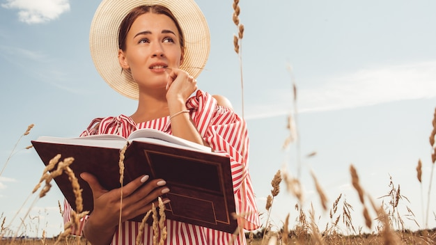 美しい女性の肖像画。フィールドで本を読みます。大学入学の準備をします。